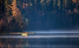 Roeiboot met mensen op wild meer Stock Foto