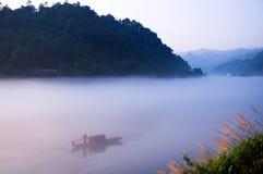 Roeien en visserij in het meer Stock Foto