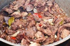 Roemeense varkensvleeshutspot die in ijzer gegoten pot wordt gemaakt stock foto's