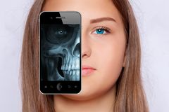Roentgen screening of the face with a smartphone. A young girl Stock Photo