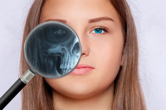 Roentgen screening with a magnifying glass, fase of a young woman Royalty Free Stock Images