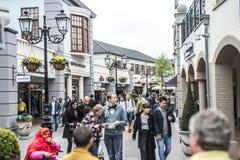 Roermond Nederländerna 07 05 2017 personer som omkring går på det Mc Arthur Glen Designer Outlet köpcentrumområdet Arkivfoto