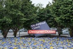Roermond, Nederland 07 05 2017 het embleem van het Ingangsteken tussen fowers van het Mc Arthur Glen Designer Outlet het winkelen Royalty-vrije Stock Fotografie