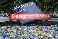 Roermond, Nederland 07 05 2017 het embleem van het Ingangsteken tussen fowers van het Mc Arthur Glen Designer Outlet het winkelen Stock Foto's