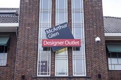 Roermond, Nederland 07 05 2017 Tekenembleem bij bakstenen muur de bouw van het Mc Arthur Glen Designer Outlet het winkelen gebied Stock Foto
