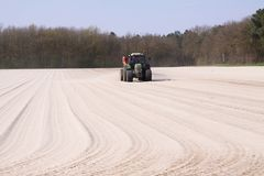 ROERMOND, NETHERLANDS - MARCH 30. 2019: Chalk fertilizer application by tractor with spreader to prepare the field royalty free stock photography