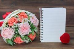 Roese花束、结婚戒指箱子和一本白皮书拷贝空间的在木背景 免版税库存照片