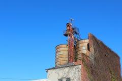 Roestende silo's en baksteenvoorgevel tegen een blauwe hemel Stock Foto