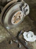 Roestig beugel voorwiel van de auto in de garage Stock Afbeelding