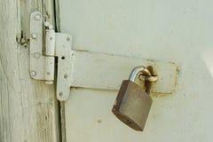 Roestig gesloten slot op oude houten witte gebarsten geschilderde deur stock fotografie