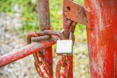 Roestig hangslotmetaal met chian op oude rode staalomheining stock fotografie