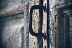 Roestig metaalhandvat op een oude houten deur stock afbeeldingen