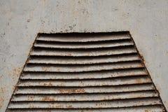 Roestig oud die ventilatietraliewerk op metaalmuur in grijs wordt geschilderd Stock Foto's