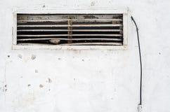 Roestig oud ventilatietraliewerk in de muur met een draad Stock Foto