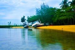 Roestig oud vissersbootschip op het stille gele zandige strand in de verse lucht van de ochtendzonsopgang stock foto's