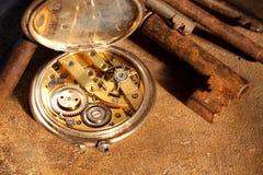 Roestig sleutels en zakhorloge stock afbeelding