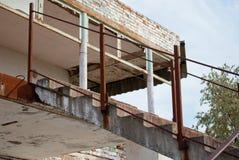 Roestig traliewerk op een verlaten gebouw tegen het hemelbouwterrein Stock Foto