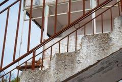 Roestig traliewerk op een verlaten gebouw tegen het hemelbouwterrein Stock Foto's