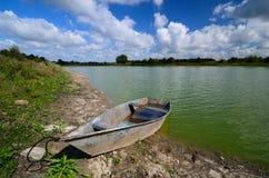 Roestige boot bij riverbank Stock Afbeeldingen
