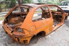 Roestige chassis van een gebrande die auto door de partij van de straat wordt verlaten Stock Foto's