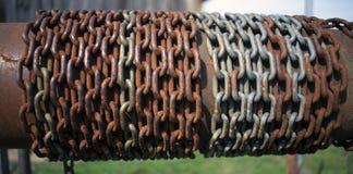 Roestige die ketting rond buis op oude waterput wordt verpakt stock afbeelding