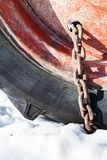 roestige die sneeuwketting aan tractorwiel wordt gepast royalty-vrije stock afbeelding