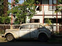 Roestige en gebroken oude die auto in een sjofele straat wordt verlaten Stock Afbeelding