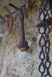 Roestige gebogen bout met noot op een oude hangerhaak stock afbeelding