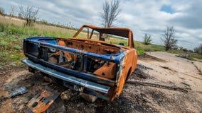 Roestige gebrande gesloopte auto Stock Foto's