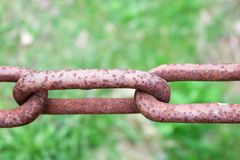 Roestige geoxydeerde bruine verbinding van een oude sterke gesmede ketting van het metaalijzer tegen een achtergrond van groen stock foto