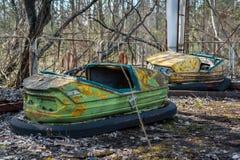 Roestige kleine kinderenauto's in verlaten pretpark in Pripyat, de uitsluitingsstreek van Tchernobyl stock foto