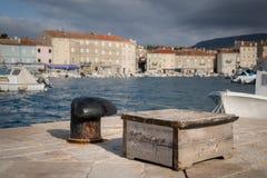 Roestige meerpaal en houten doos in de haven van Cres Stock Foto