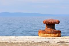Roestige meertrosmeerpaal op haven van Podgora Stock Afbeelding