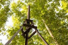 Roestige metaalmast op een achtergrond van groene bomen royalty-vrije stock foto's