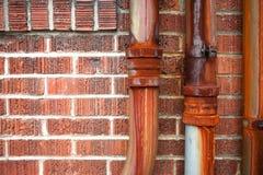 Roestige metaalpijp op rode bakstenen muur Stock Afbeelding