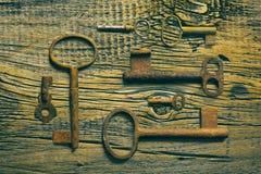 Roestige middeleeuwse sleutels op uitgeputte houten lijst Royalty-vrije Stock Fotografie