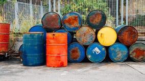 Roestige olievatentrommels stock fotografie