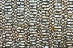 Roestige omheining en witte steen Stock Fotografie