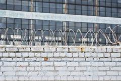 Roestige omheining met prikkeldraad op achtergrondgevangenis of installatie stock foto