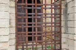 Roestige omheining in venster van middeleeuws huis stock fotografie