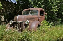 Roestige oude die bestelwagen in gras wordt verborgen stock afbeelding