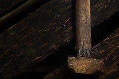 Roestige oude hamer op natte zwarte houten achtergrond Stock Fotografie