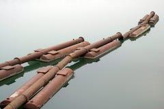 Roestige pijpen in het water Stock Afbeelding