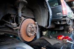 Roestige remschijf op autokerkhof stock foto