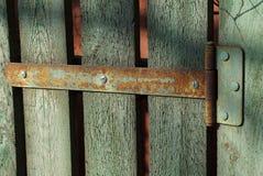 Roestige scharnier op groene houten omheiningsraad stock foto