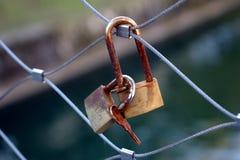 Roestige sleutels en sloten op een metaalbrugomheining stock afbeelding