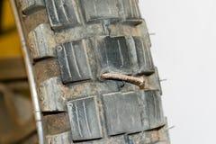 Roestige spijker in motorfietsband Stock Fotografie