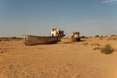 Roestige vissersboten die in het zand liggen Stock Afbeelding