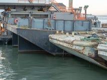 Roestige vrachtschepen en boten onder materiaalzitting bij industrieel dok stock foto