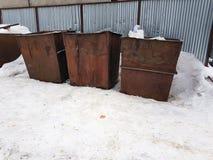 Roestige vuilnisbakken op de sneeuw in de winter royalty-vrije stock afbeeldingen